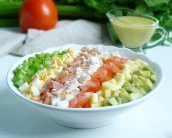 кобб салат в тарелке на столе, на фоне соусница с горчичным соусом, свежий помидор, зелень сельдерея