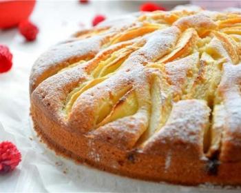 бисквитный корнуэльский яблочный пирог, присыпанный сахарной пудрой на белой подставке на белом столе с красными цветами