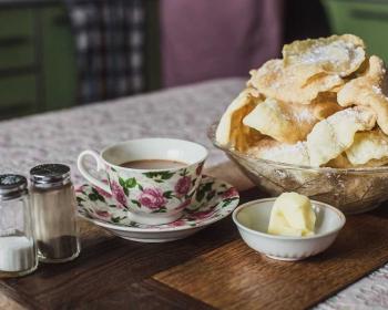 ломтики хрустящего кош-теле в прозрачной пиале, рядом чашка с чаем на блюдце, масло в маленькой пиале, соль и перец в баночках на столе