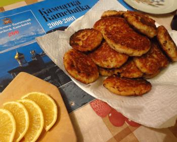 котлеты из кальмаров сложены горкой на бумажном полотенце, рядом лежит дощечка с ломтиками лимонов