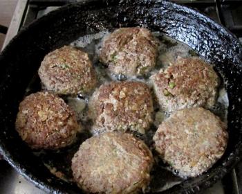 семь жареных котлеток из свиной печени с рубленой зеленью на сковороде с маслом на плите