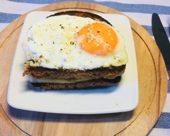 бутерброд Крок-мадам из яиц и хлеба на квадратной белой тарелке на круглой деревянной разделочной доске