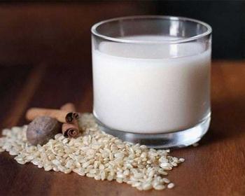 кунжутное молоко в сткане на столе, рядом рис, палочки корицы, мускатный орех