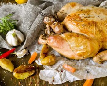 курица гриль, запеченная в духовке целиком, на пергаментной бумаге, рядом несколько долек печеного картофеля, головка чеснока, стручок горького перца и несколько долек моркови