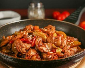 жареные кусочки куриного филе с баклажанами и сладким перцем в сковороде на круглой деревянной разделочной доске