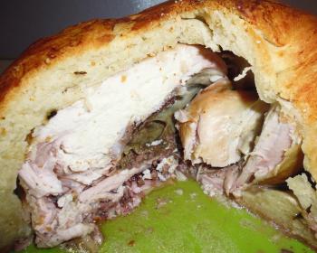 разрезанный пирог с курицей внутри на зеленой тарелке