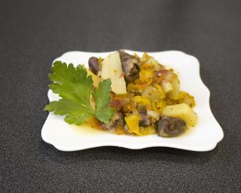 тушеные куриные сердца с картофелем и овощами в белой квадратной тарелке на столе