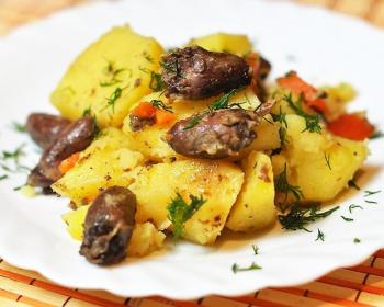 куриные сердечки с картошкой, тушеные в мультварке, наложены в плоскую белую тарелку