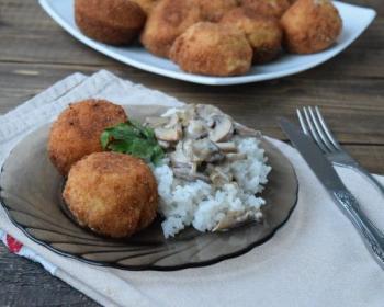 два жареные куриные шарика с вареным рисом, грибами и листиками петрушки на плоской стеклянной тарелке на столе, покрытом полотенцем, рядом нож с вилкой