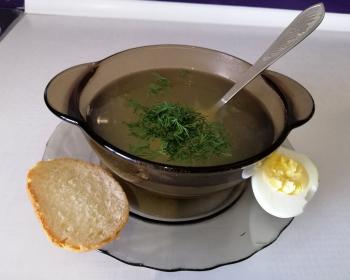 куриный бульон с овощами, присыпанный измельченным укропом, в тарелке рядом с сухариками и половинкой вареного яйца