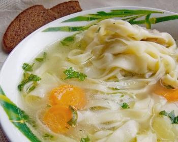 суп с лапшой, морковью и зеленью в белой тарелке, рядом ломтик черного хлеба