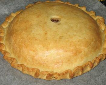 на столе лежит круглый курник из блинов с курицей и грибами, в середине пирога дырочка