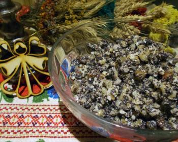 кутья из перловки с маком и изюмом в прозрачной тарелке на столе, застеленном вишитой скатретью с новогодними украшениями