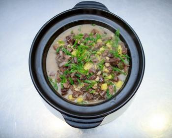 куырдак с кусочками мяса и картофелем, присыпанный рубленой зеленью, в миске на столе