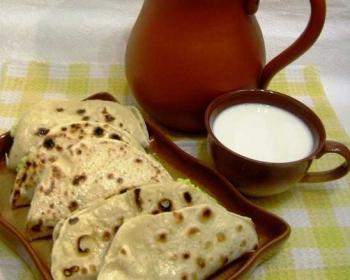 пять кыстыбыев с пшенкой в тарелке на столе, рядом глинянная кружка с молоком и глиняный кувшин