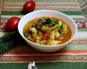 лагман из баранины в тарелке на столе, застеленном полосатой скатертью, на фоне пучок свежего укропа и два свежих помидора