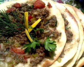 лахмаджун из запеченных лепешек с кусочками мяса и овощей с зеленью, сложенных друг на друга