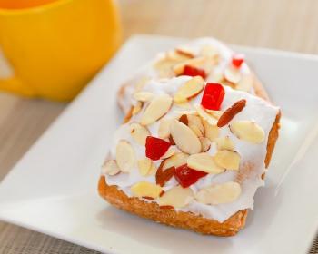 два запеченных печенья, смазанных кремом и присыпанных рублеными орешками, на белой плоской тарелке на столе