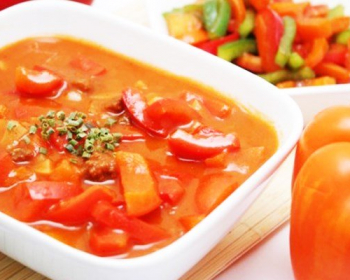 лечо из болгарского перца с томатной пастой, присыпанное рубленой зеленью, в белой тарелке на столе