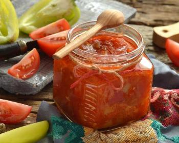 лечо из перца и помидоров в небольшой стеклянной баночке, сверху которой лежит деревянная ложка, рядом с банкой разрезанные на четвертинки помидоры и на половинки перцы