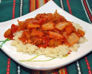 вареный рис с лечо из кусочков баклажанов, помидоров и сладкого перца на белой тарелке на столе, застеленном скатертью