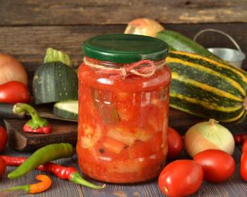 лечо с кабачками и перцем на зиму, заготовленное на зиму в банках, стоит на столе в окружении свежих овощей