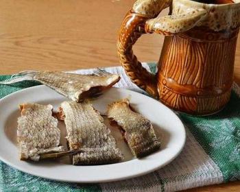 кусочки вяленого леща в тарелке, стоящей на столе, укрытом салфеткой, на фоне пивной бокал