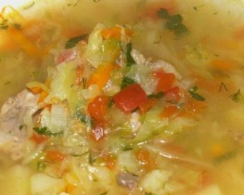 щи с капустой, картошкой, кусочками мяса, помидорами и морковью, посыпанные рубленой зеленью, в тарелке
