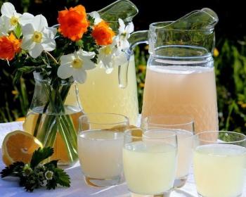 лимонный и клубничный квас в графинах на столе, рядом стоят стаканы с напитком и ваза с цветами