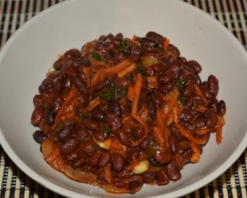 лобио из красной фасоли, тертой моркови и зелени в белой тарелке на столе, застеленном деревянным ковриком
