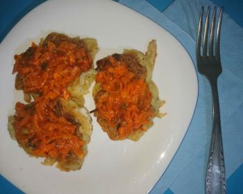 три луковых оладушка с морковно-томатным соусом в белой тарелке на столе