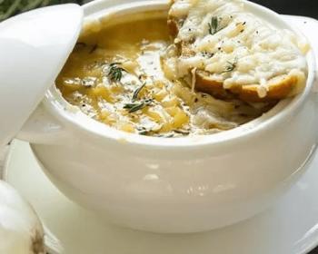 луковый суп в супнице, рядом лежит крышечка, сверху на тарелке лежит гренка с сыром