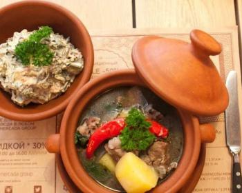 лывжа из баранины с картофелем, украшенная зеленью и красным горьким перцем, в глиняном горшке, на краю посуды лежит глиняная крышка, рядом столовый нож и глиняная миска с заправкой