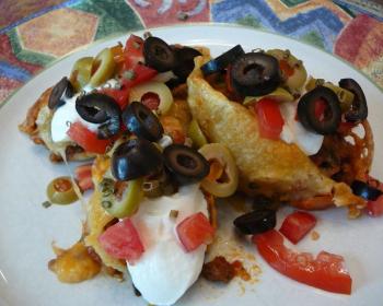 макароны, фаршированные фаршем, с добавлением кусочков оливок, маслин и свежих помидоров в тарелке на столе