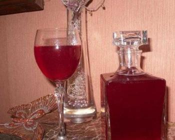 малиновая настойка в хрустальном графине, рядом стоит бокал с малиновой наливкой