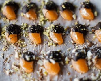 на пергаментной бумаге лежать дольки мандаринов в шоколаде, присыпанные грецкими орехами