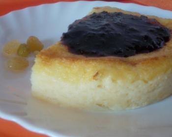 треугольный кусочек манного пудинга с вареньем на тарелке, рядом лежит изюм