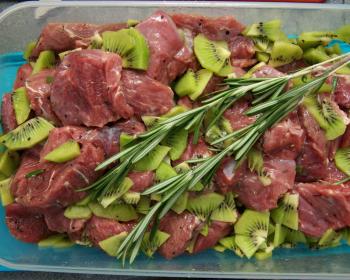 кусочки мяса с киви и веточками розмарина в емкости