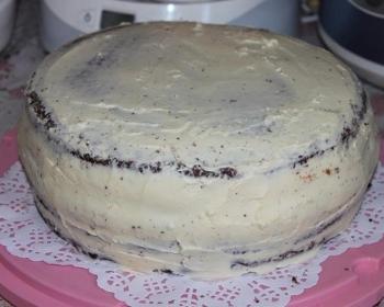 торт, смазанный масляным кремом со сгущенкой, на розовой подставке на столе