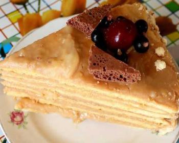 треугольный кусочек медовика со сгущенкой, украшенный кусочками шоколада и ягодами, в блюдце на столе