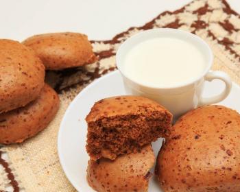 медовые пряники на белой плоской тарелке и на столе с кружкой молока