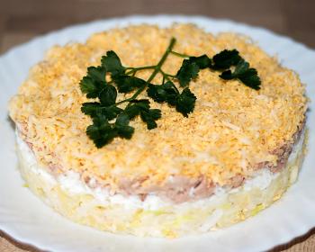 слоеный салат мимоза с печенью трески, яичными желтками и майонезом, украшенный зеленью, на белой тарелке на столе