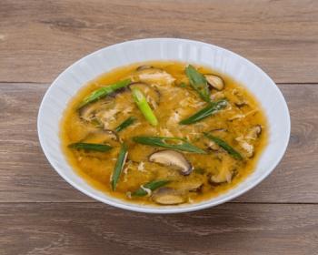 в белой пиале лежит мисо суп с луком порей и шиитаке