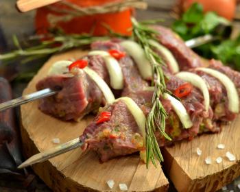 кусочки мяса с луком на шампурах на доске, украшенные зеленью