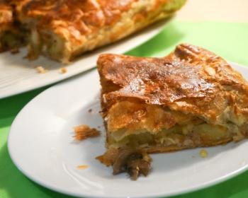 кусок мясного пирога из слоеного теста на белой тарелке на зеленом столе, на фоне остальная часть пирога