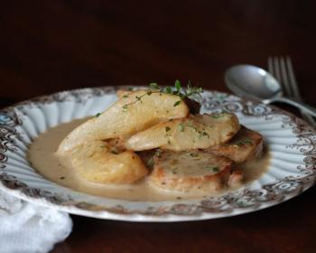 тушеные кусочки свинины с дольками груш, политые соусом и украшенные веточкой зелени, на белой тарелке на столе, рядом ложка с вилкой