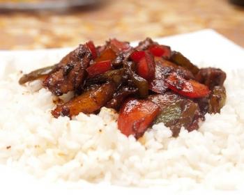 жареные кусочки мяса в кисло-сладком соусе с овощами, выложенные на отварной рис, на тарелке