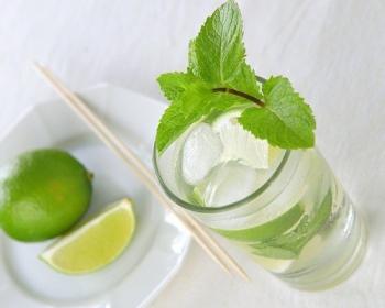 на столе стоит стакан с алкогольным мохито,внутри плавает лед, сверху лежит веточка мяты, рядом на тарелке лежит целый лайм и долька, и две деревянные шпажки