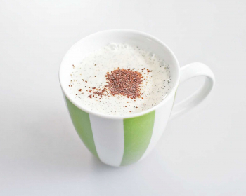 молочный кисель, присыпанный тертым шоколадом, в полосатой кружке