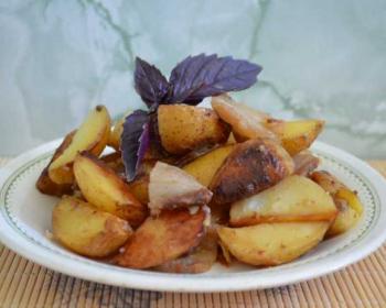 молодой картофель в рукаве, запеченный до золотистого цвета, с кусочками сала на белой тарелке, украшенный веточкой базилика